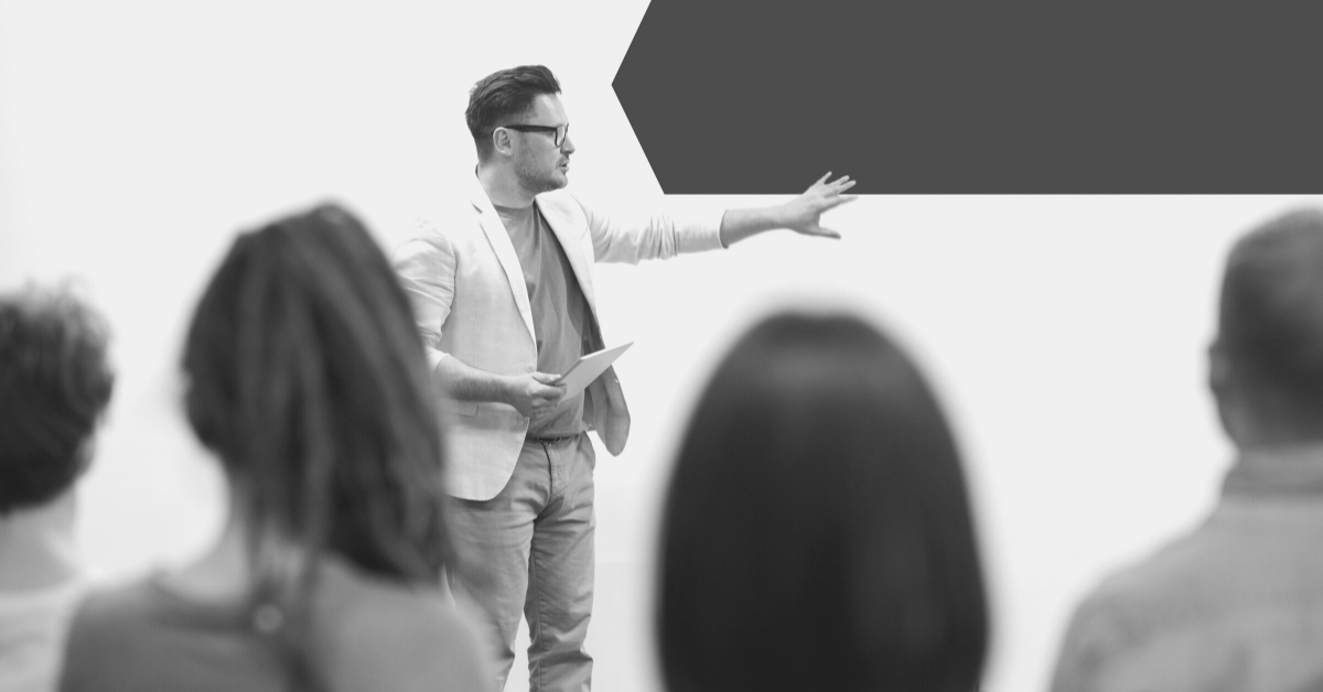 Man stood in front of group of people explaining outplacement services
