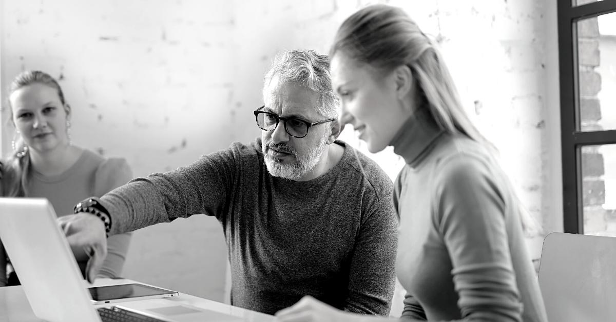 Redundancy Management: Man sat down pointing at laptop next to woman