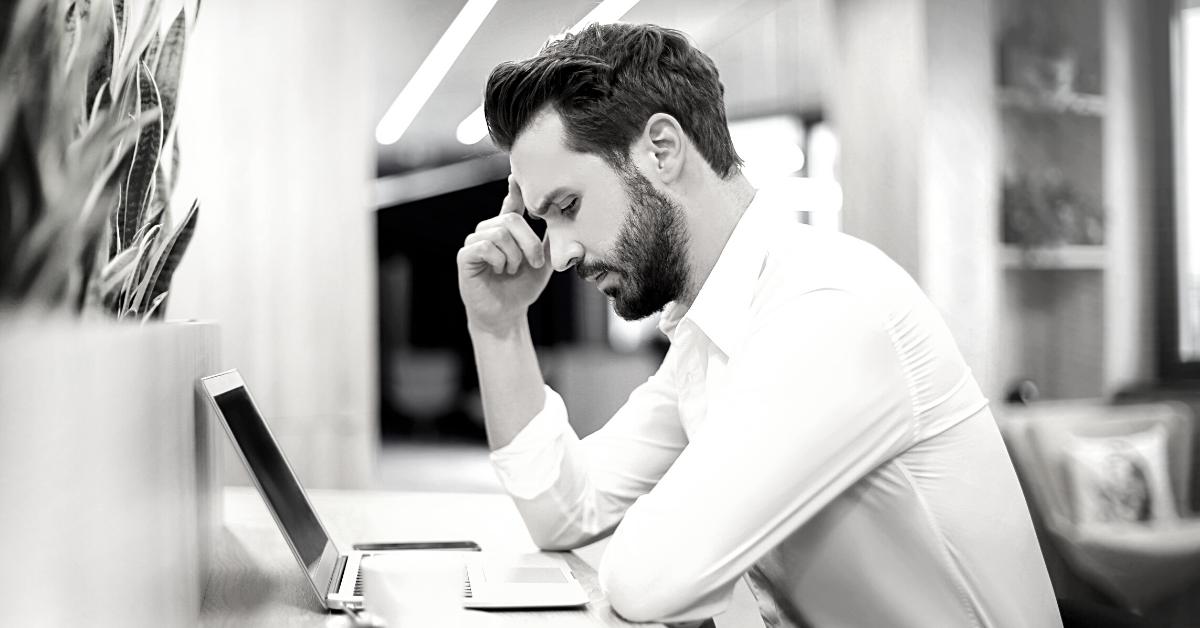 Man sat at laptop after being made redundant